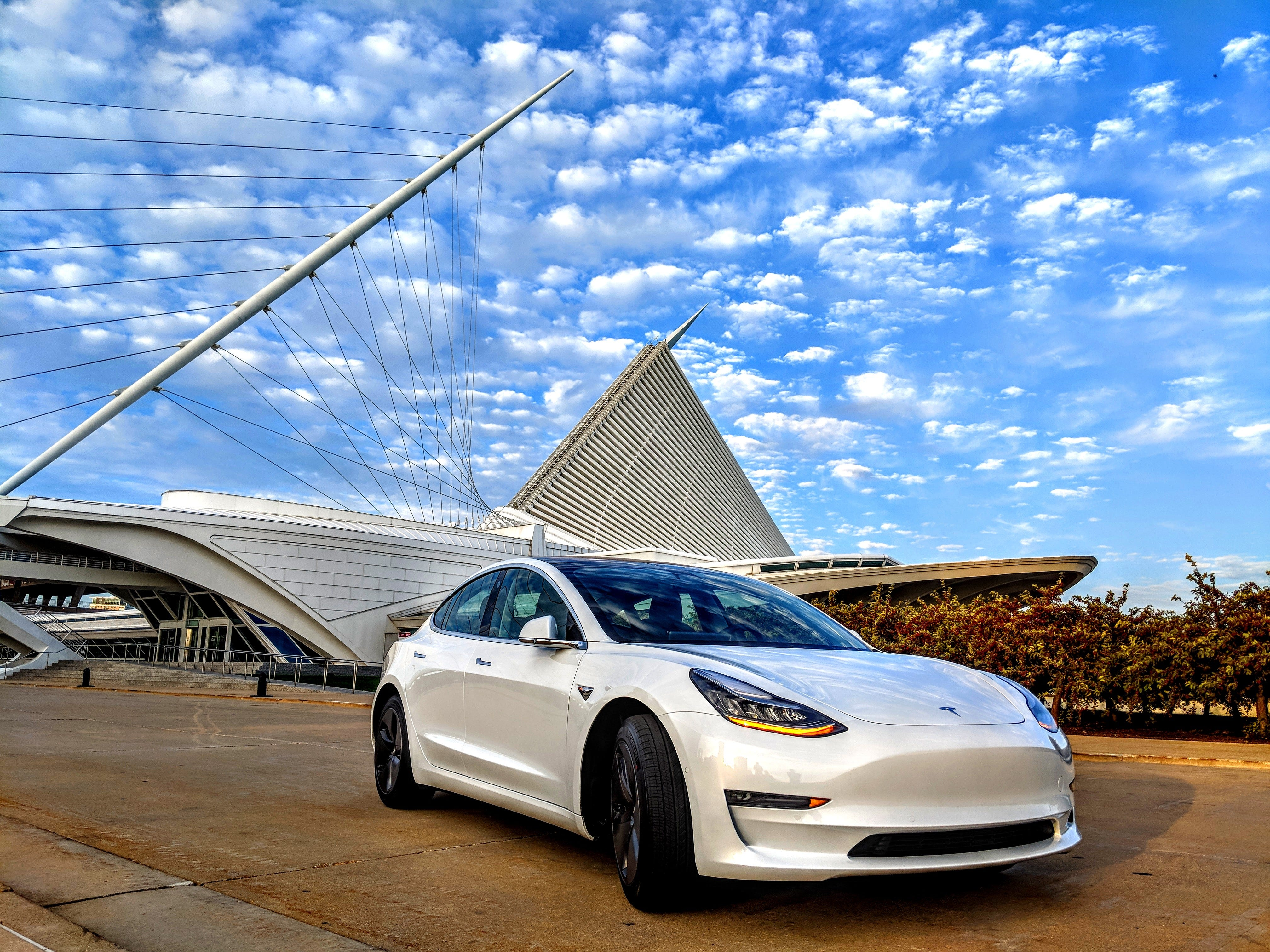 "Gaurav Mahendru shared his picture of ""Pearl,"" a Tesla Model 3 in Pearl White with 18-inch Aero Wheels, outside the iconic Milwaukee Art Museum.   His family got the car last September after waiting 17 months. They were among those who reserved the car before it was in production.   ""We have already done 5,000 miles on it! We had a 2004 Toyota Camry before this and we were past due for an upgrade....We are so much in love with this car that we are never going back to gas cars ever again.""  Aside, from the car being electric, its safety record, design and being a tech gadget ""built around a computer,"" he feels a part of something bigger:   ""The feeling of being a part of a movement!"""