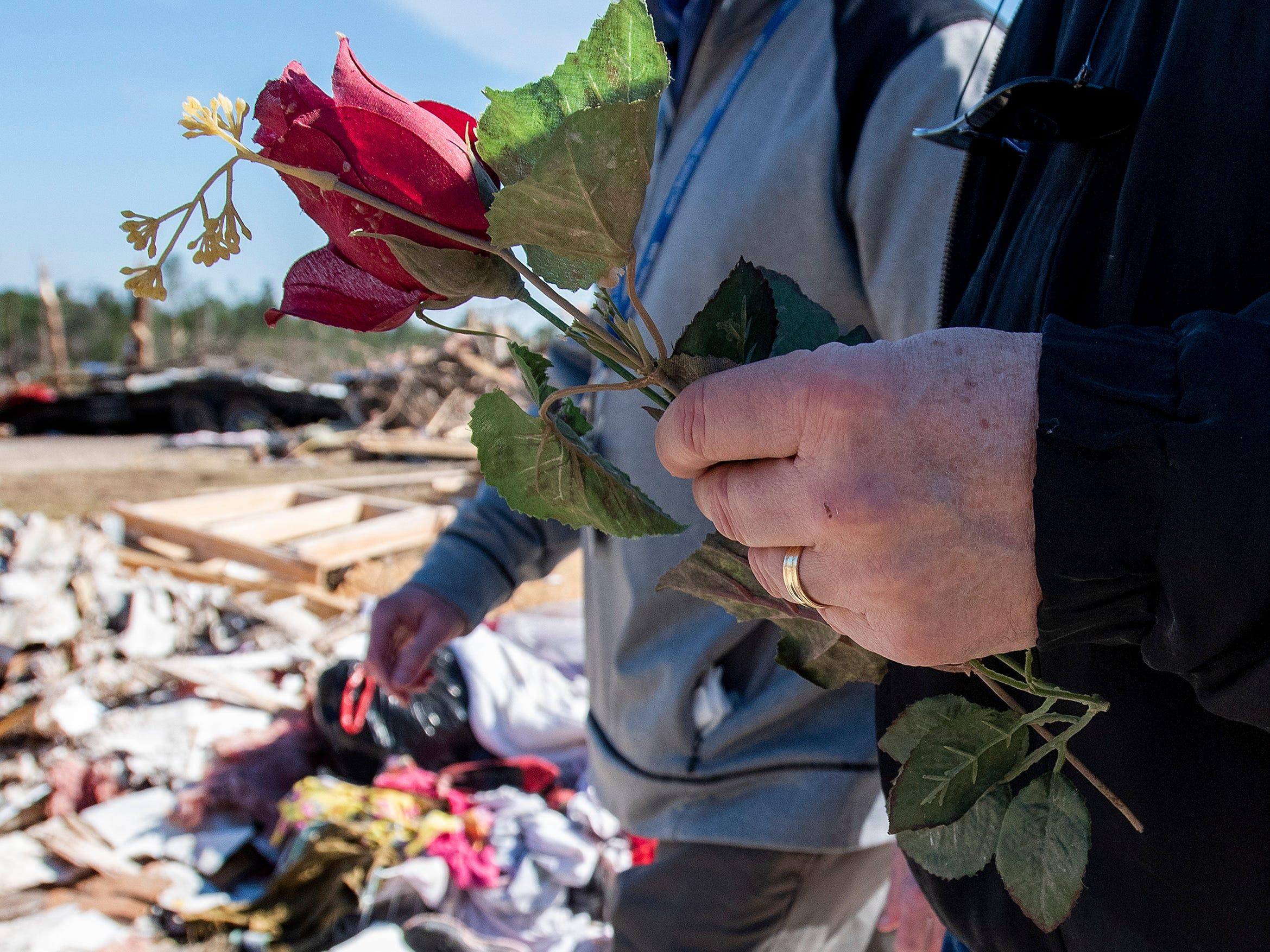 Sen. Doug Jones, D-Ala., carries a plastic rose he picked up among the debris in Beauregard, Ala., on March 7, 2019.