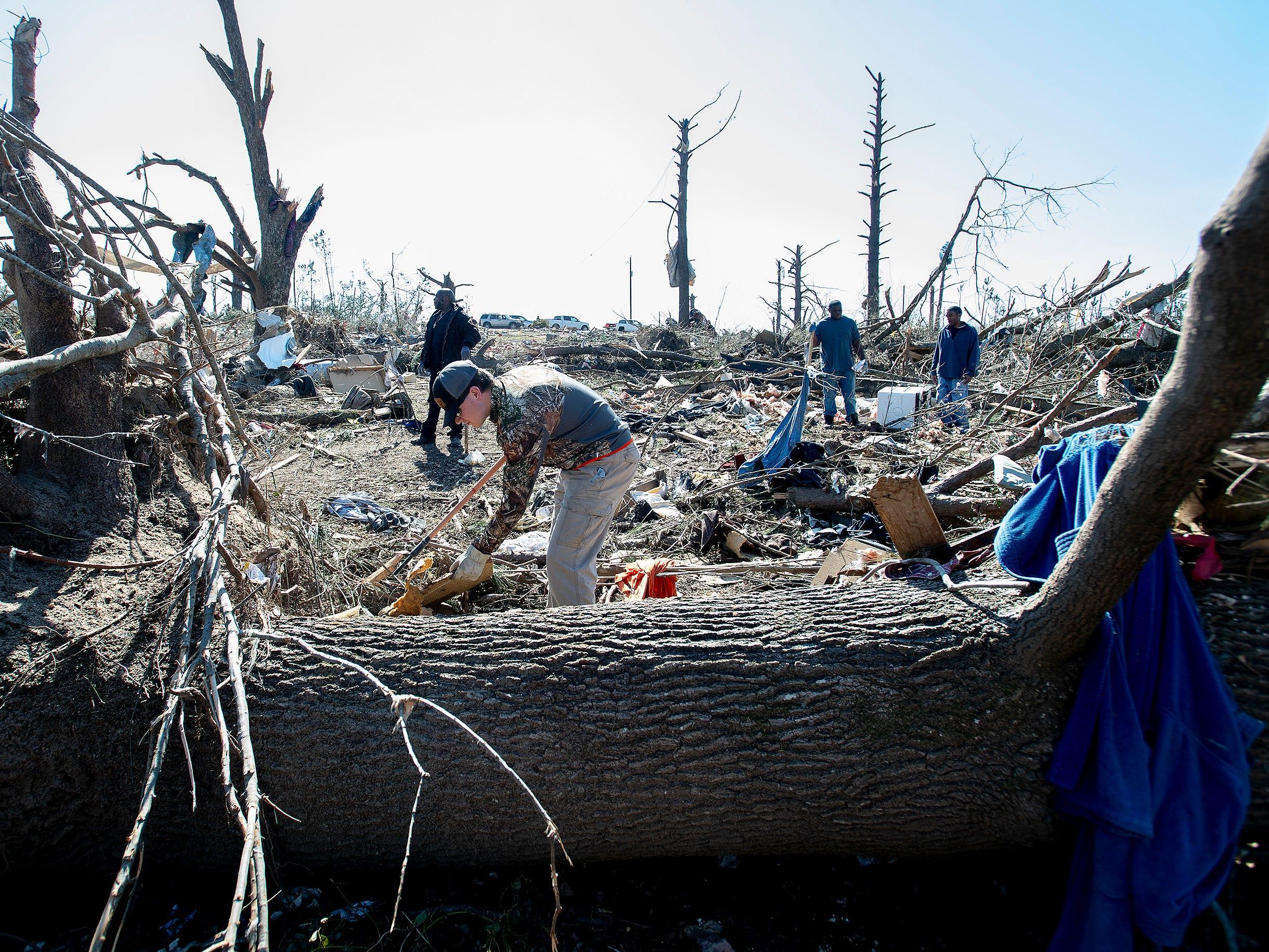Volunteers look for valuables among the debris in Beauregard, Ala., on March 7, 2019.