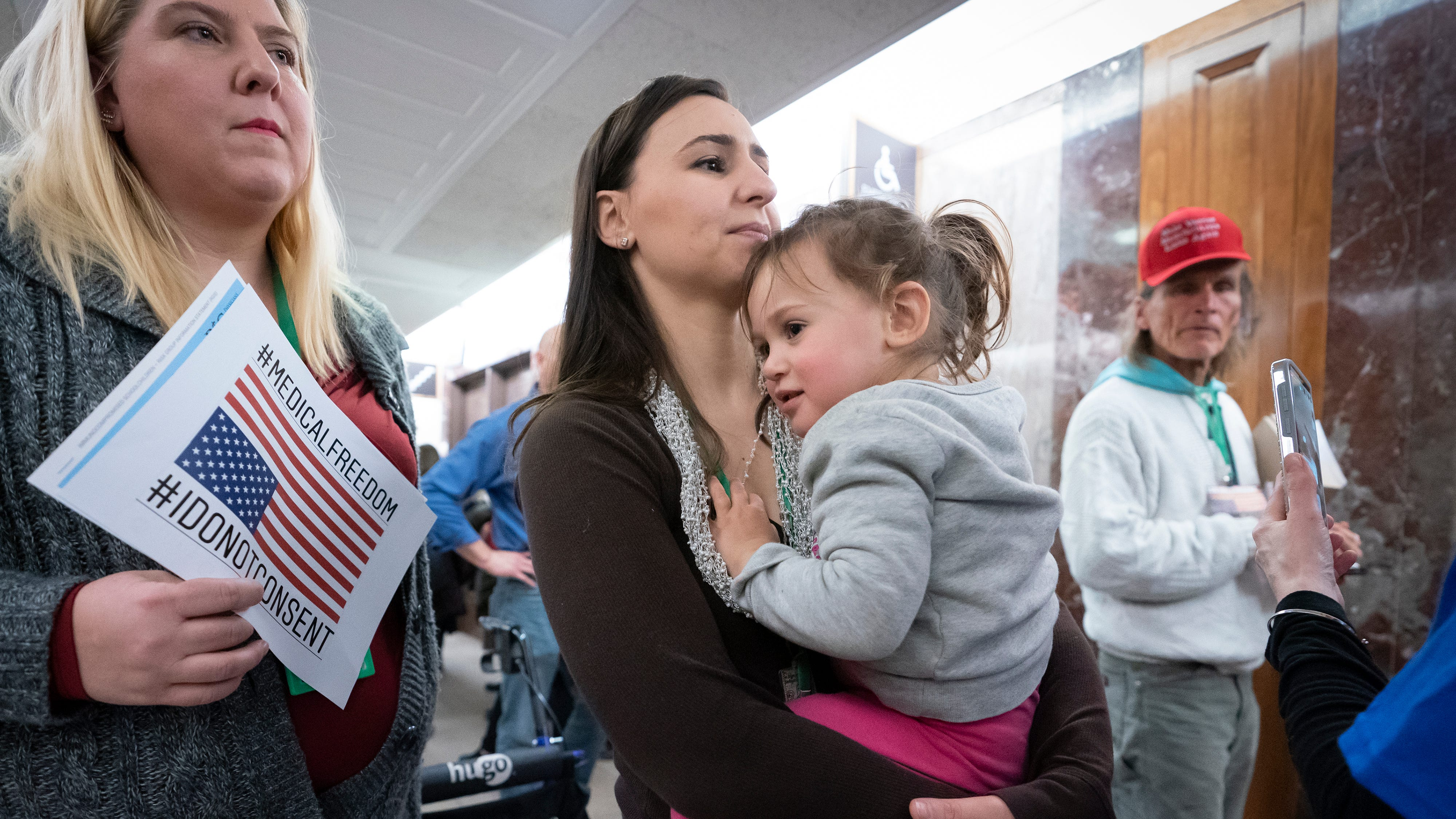 Sarah Myriam of New Jersey holds her daughter Aliyah, 2, as they join activists opposed to vaccinations outside a Senate Health, Education, Labor and Pensions Committee hearing on the safety of vaccines on March 5, 2019.