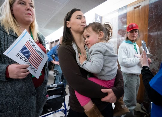Sarah Myriam of New Jersey holds her daughter Aliyah, 2, as they join activists antagonistic to vaccinations open air a Senate Health, Training, Labor and Pensions Committee listening to on the safety of vaccines on March 5, 2019.