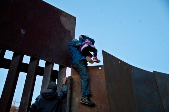 A Honduran migrant helps a young girl cross to the American side of the border wall, in Tijuana, Mexico on Dec. 2, 2018.