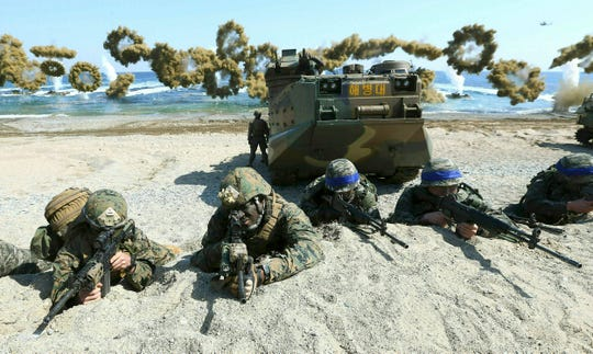 In this March 12, 2016, file photo, Marines of the U.S., left, and South Korea, wearing blue headbands on their helmets, take positions after landing on a beach during the joint military combined amphibious exercise, called Ssangyong, part of the Key Resolve and Foal Eagle military exercises, in Pohang, South Korea.