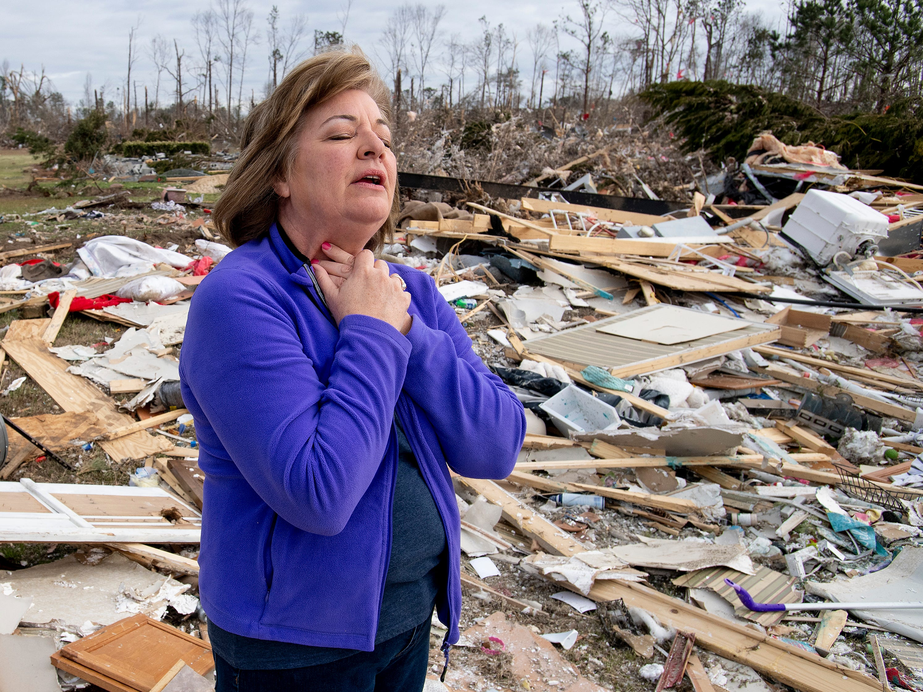 Cindy Sanford recounts barely escaping the Sunday tornado as she stands among the debris that was her home in Beauregard, Ala., on Friday March 8, 2019.