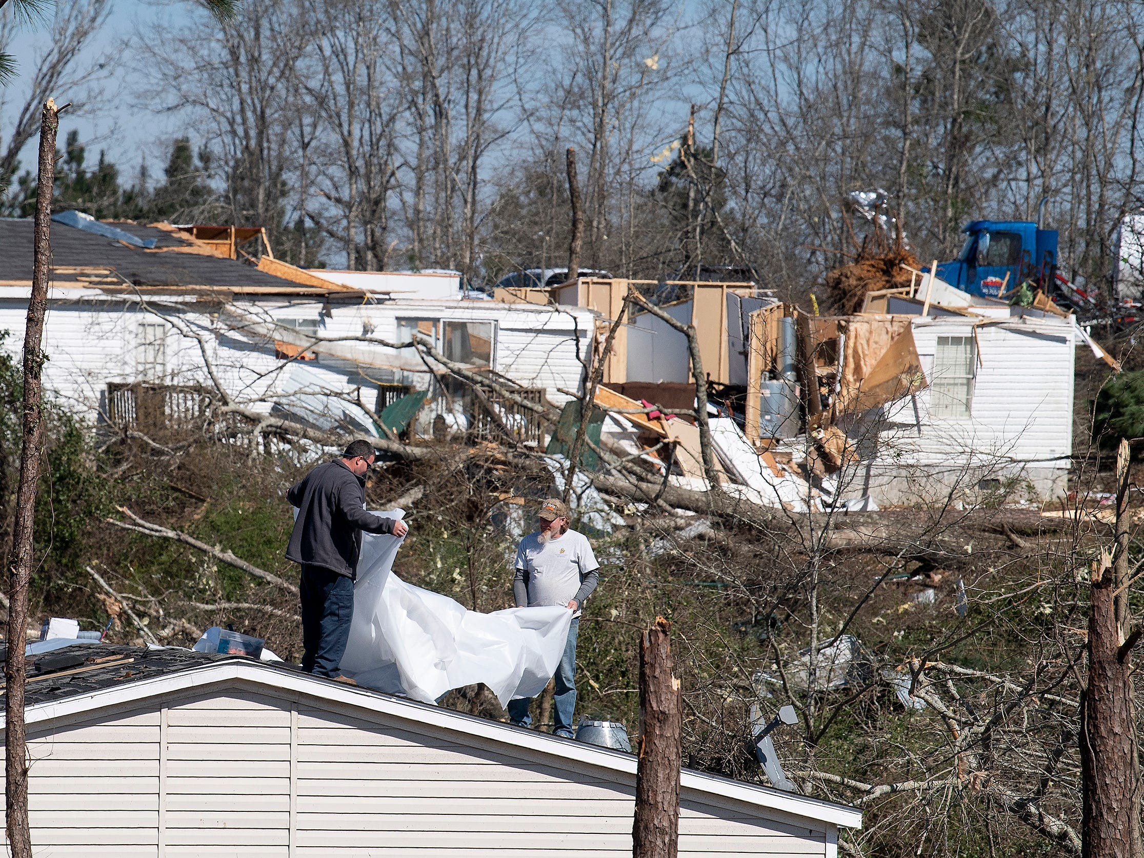 Residents cover the damaged roof of a mobile home in Beauregard, Ala., on March 7, 2019.