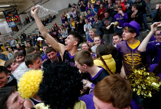 Denmark's Patrick Suemnick waves the game net in a crowd of fans and players after the Vikings' 46-41 win over Freedom on Saturday at Appleton North.