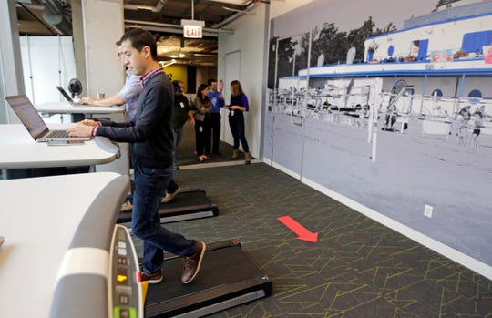 In this file photo employees work at treadmill desks in the new Google Chicago office. Goldman Sachs pinned a poll to its Twitter account asking what its employees should wear to work now that the investment bank has relaxed its dress code.