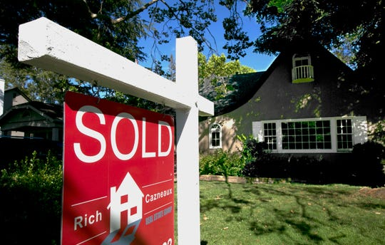 """This 2017 file photo shows a """"Sold"""" sign displayed in front of a house in Sacramento, Calif. A home of your own comes with new freedom and more responsibility."""