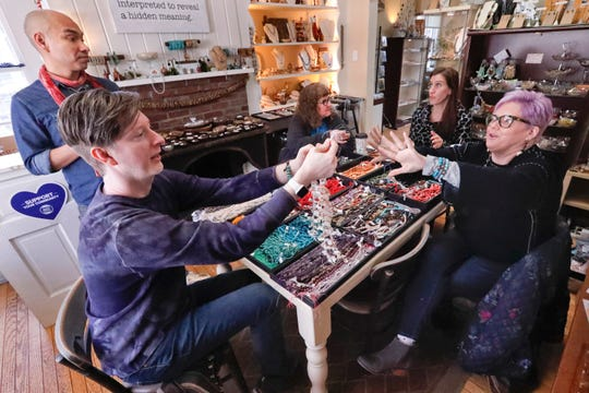 A customer at Allegory Gallery, Denise Glover, right, hands her selections to William Jones, one of the co-owners of the jewelry and art store, as fellow owner Andrew Thornton, left, talks with instructor Laurel Ross, center right, and client Cindy Kuhns, center left, in the small town of Ligonier, Pa. Social media is a resource Thornton and Jones use to stay on top of trends by connecting with customers.