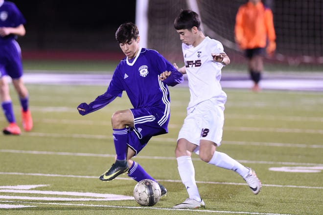 Wylie's Franky Becerra (14) tries to keep the ball away from a Wichita Falls High defender at Bulldog Stadium on Friday, March 8, 2019.