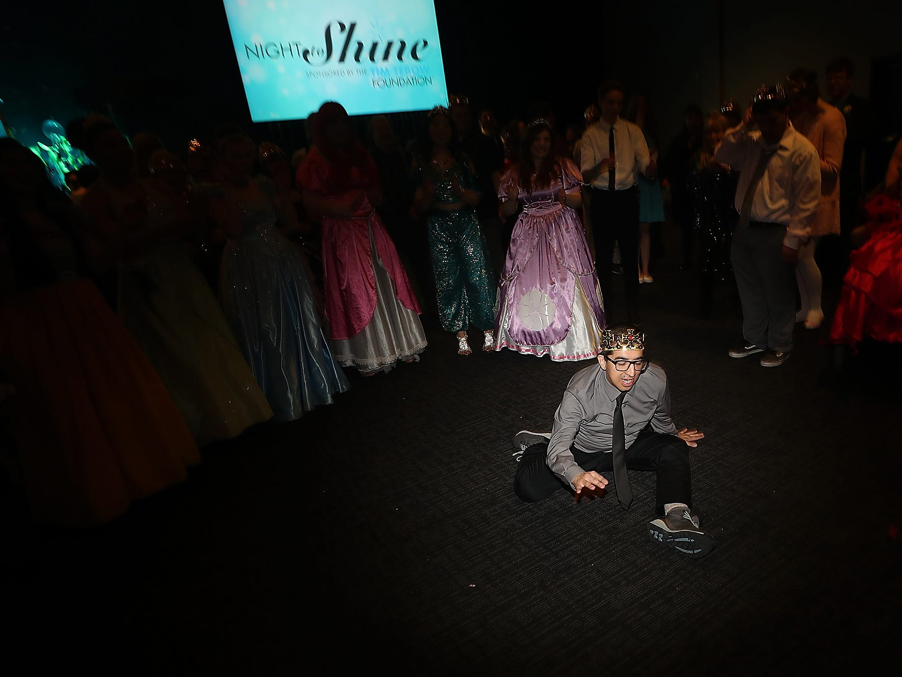 Charlie Yang hits the floor as he attempts the splits while dancing during the Night To Shine at the newlife Training & Events Center in Silverdale on Friday, March 8, 2019.