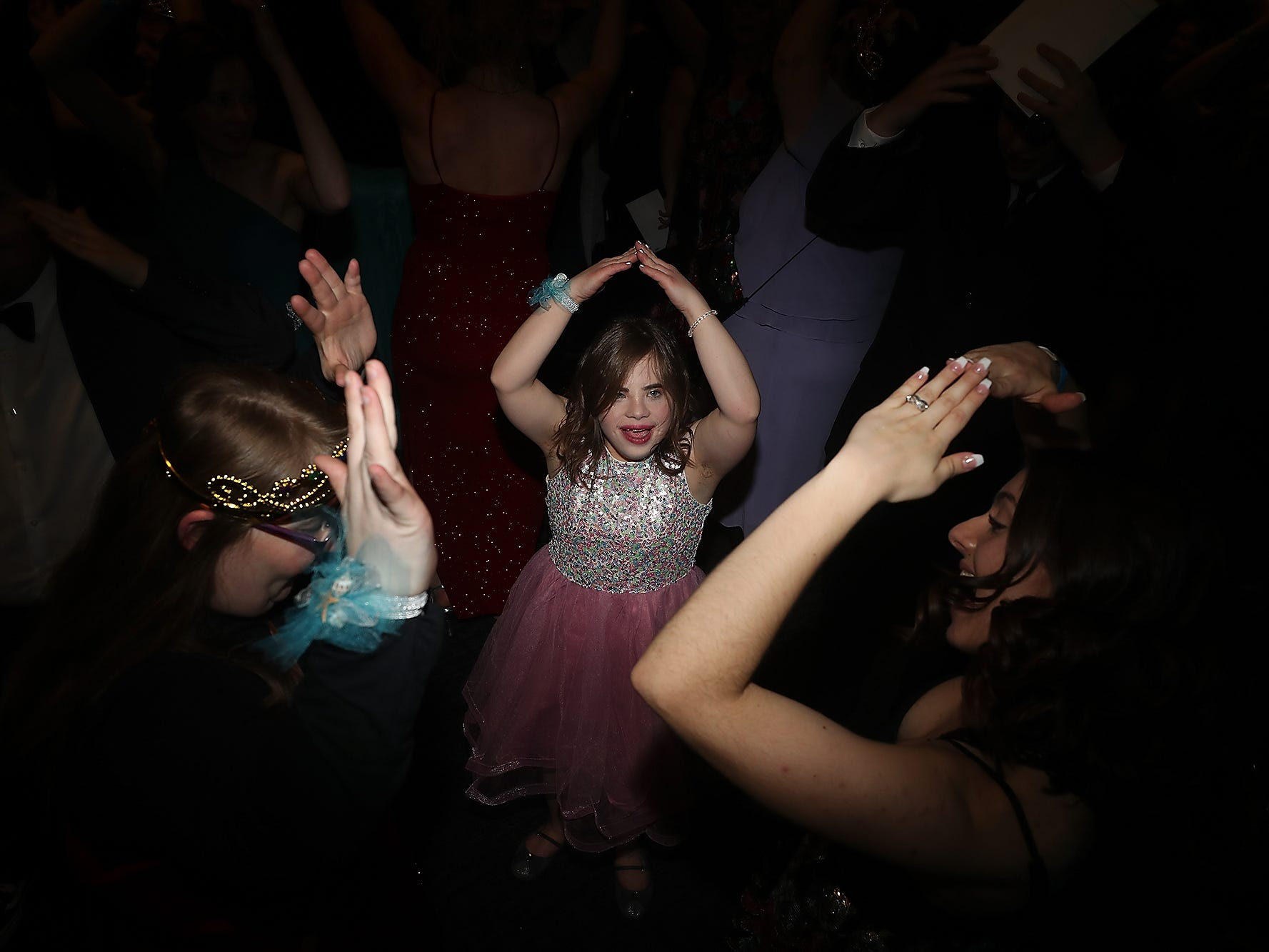 Hannah LaCelle , center, and buddy Sariana Rohlinger, right, dance the YMCA during the Night To Shine at the newlife Training & Events Center in Silverdale on Friday, March 8, 2019.