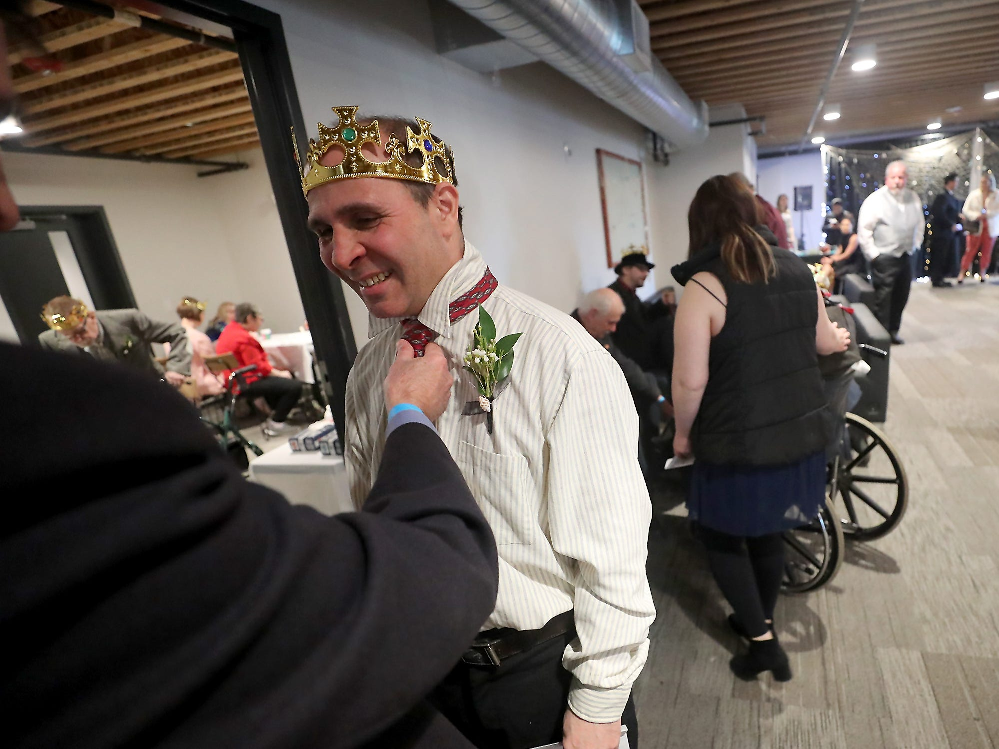 Night To Shine prom attendee Sean Garrity, of Bremerton, gets his tie on and straightened with the help of volunteer Bruce Coles at the newlife Training & Events Center in Silverdale on Friday, March 8, 2019.