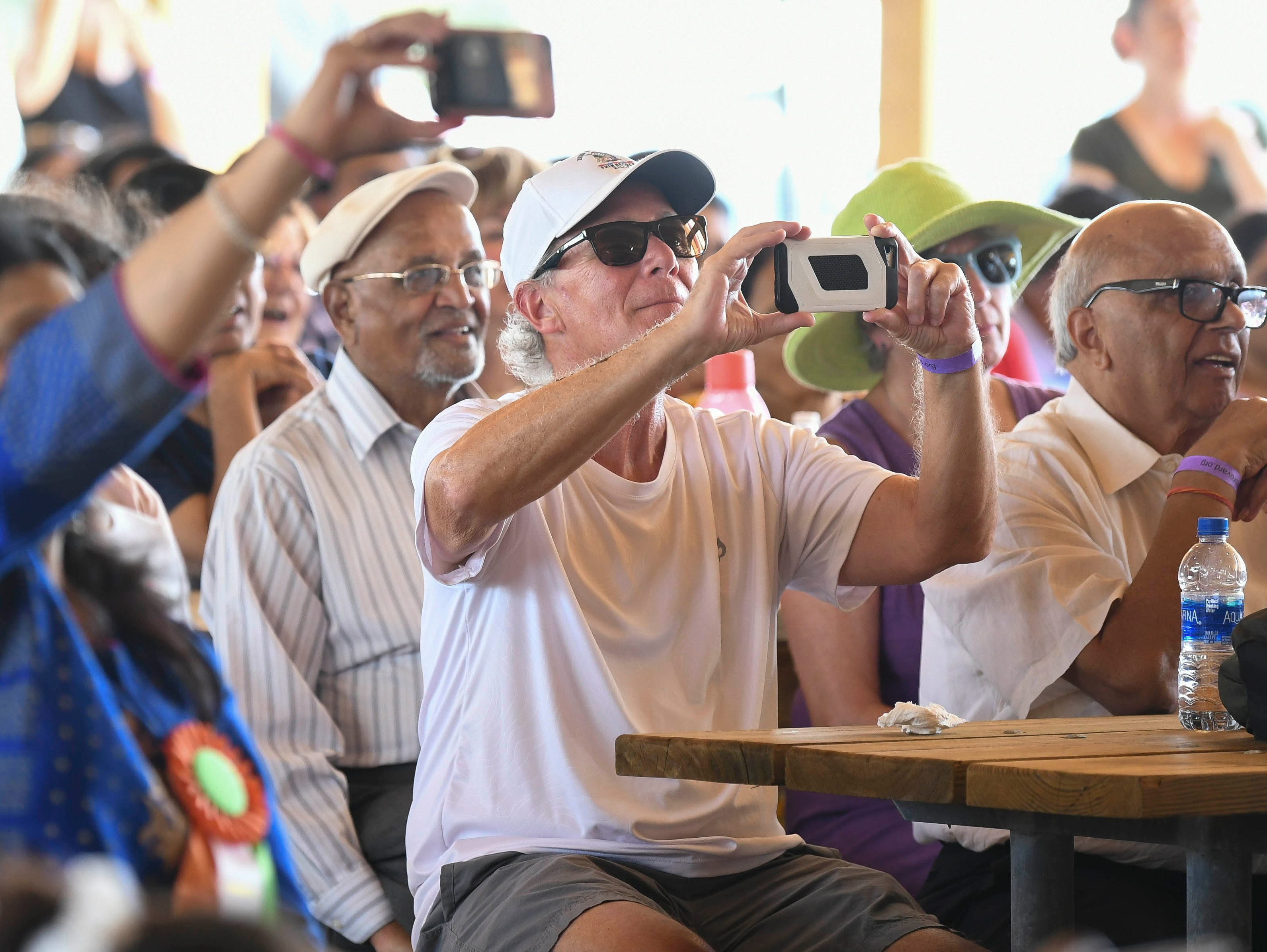 Spectators take pictures of the performers on stage at Indiafest Saturday at Wickham Park's main pavilion.