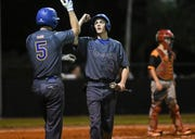 Trey Felker high fives teammate Jackson Woodward after he scored in a game against Cocoa