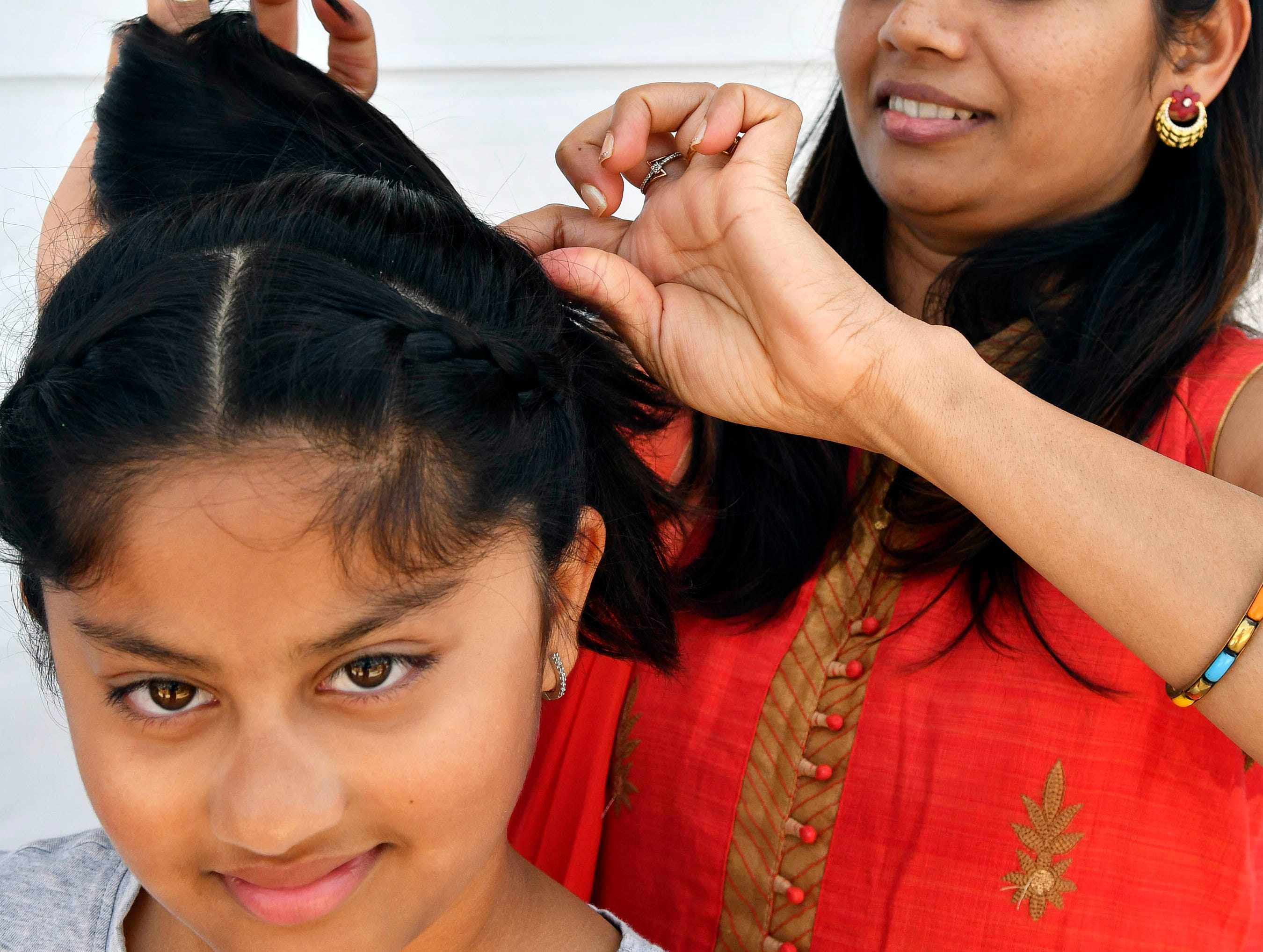Kajal Mehta works on her daughter Twisha's hair before she performs Saturday at Indiafest at Wickham Park's main pavilion.