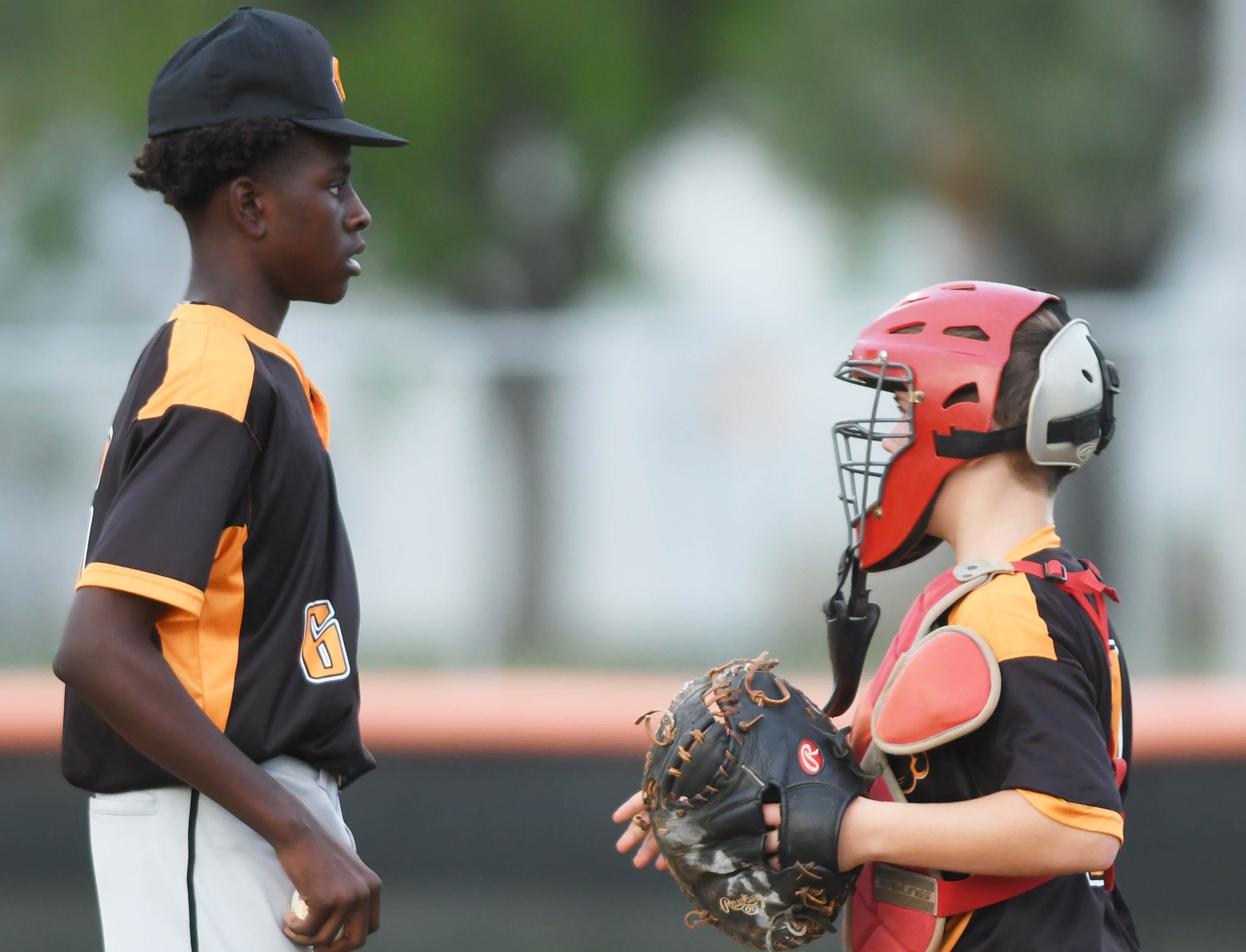 Cocoa pitcher Amarion James-Williams talks with his catcher Clint Sturgill during Friday's game against Titusville.