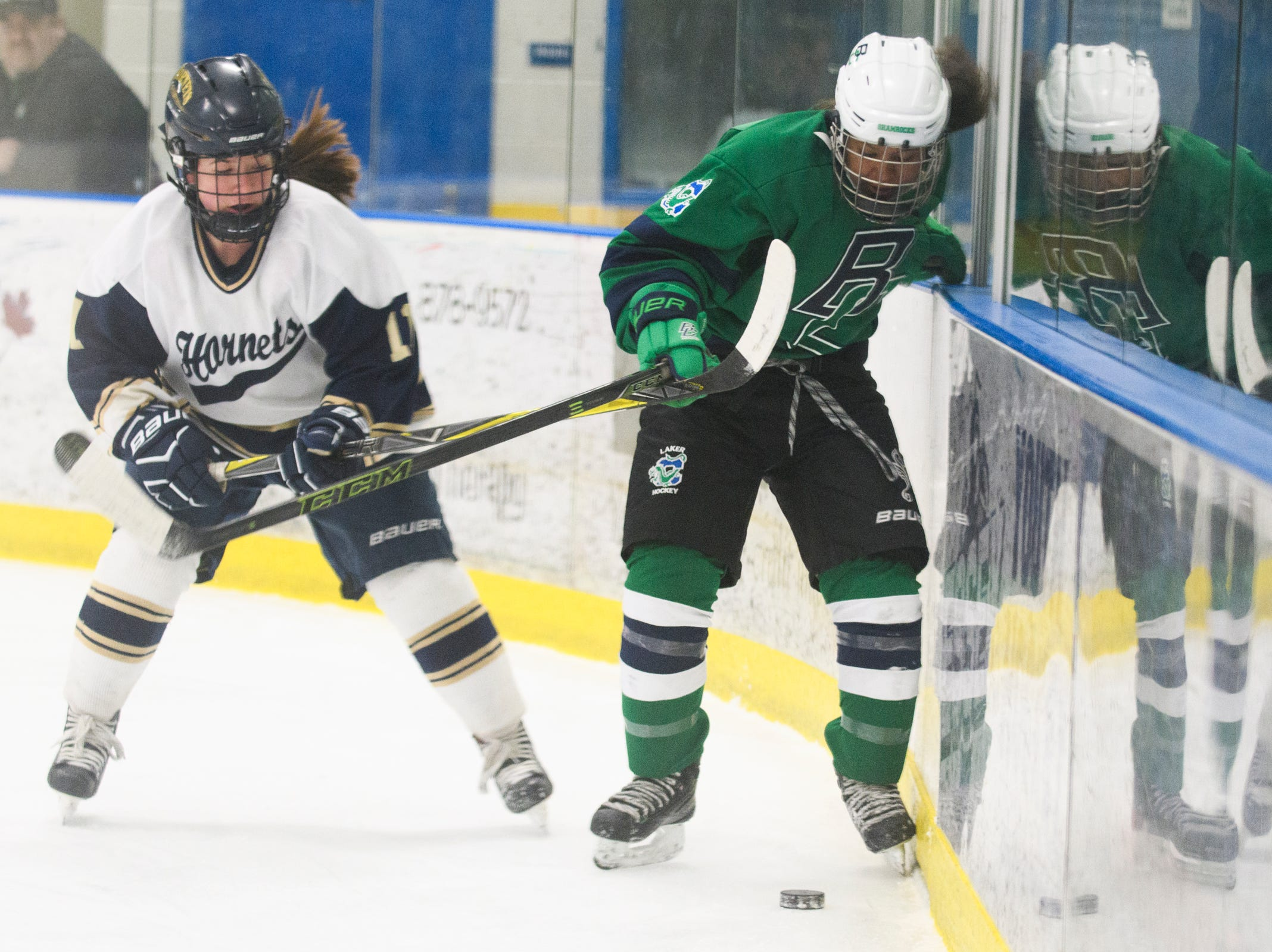 Essex's Francesca Martin (11) battles for the puck with Burlington/Colchester's Lane Sky (11) during the girls semi final hockey game between the Burlington/Colchester Sea Lakers vs. Essex Hornets at Essex skating rink on Saturday afternoon March 9, 2019 in Essex, Vermont.