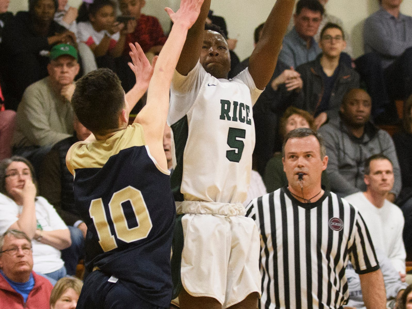 Rice's Mo Awayle (5) shoots the ball over Essex's Aiden Paquette (10) during the boys quarterfinal basketball game between the Essex Hornets and the Rice Green Knights at Rice Memorial High School on Friday night March 8, 2019 in South Burlington, Vermont.