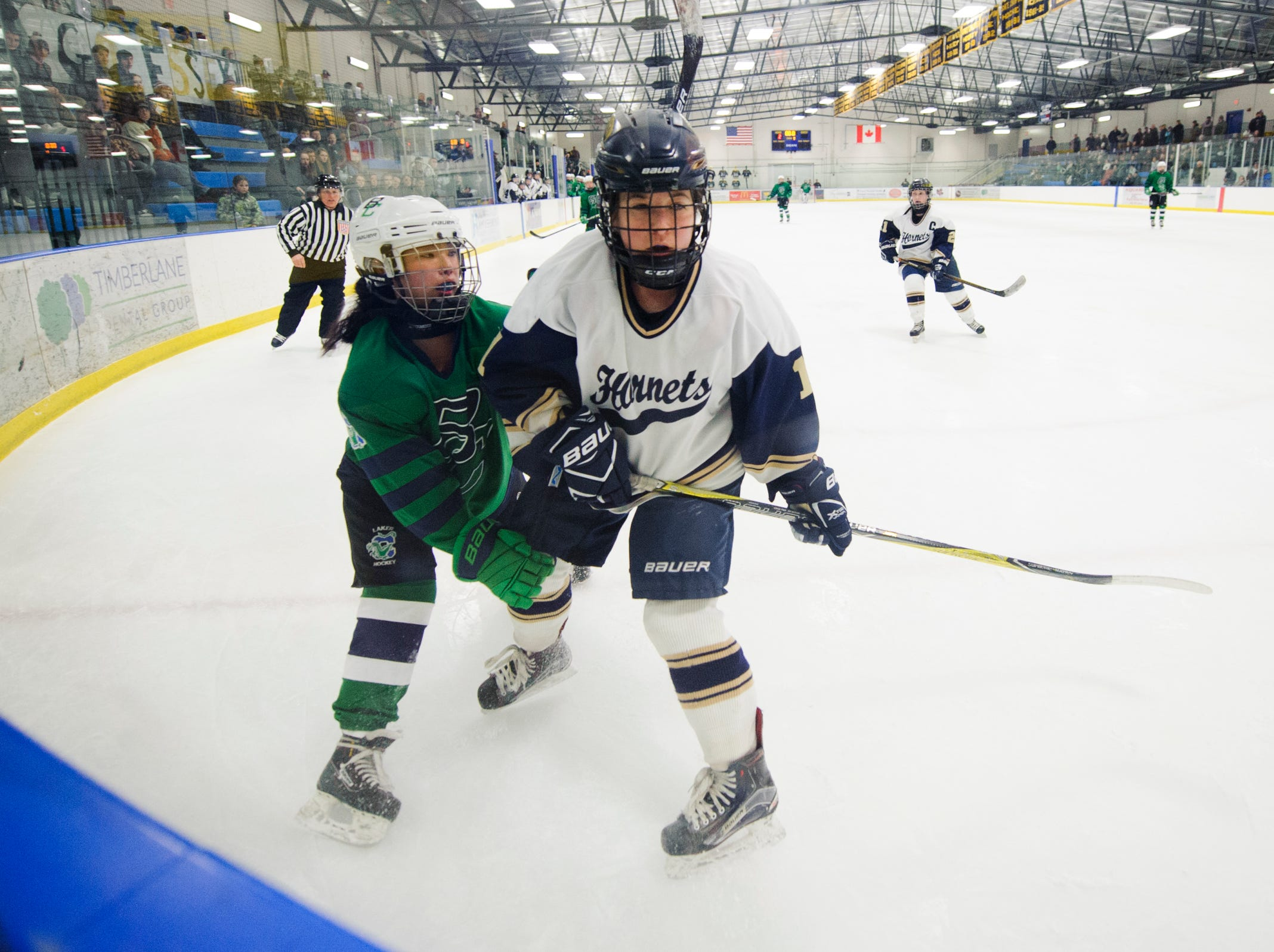 Burlington/Colchester's Olivia Maher (10) battles for the puck with Essex's Francesca Martin (11) during the girls semi final hockey game between the Burlington/Colchester Sea Lakers vs. Essex Hornets at Essex skating rink on Saturday afternoon March 9, 2019 in Essex, Vermont.