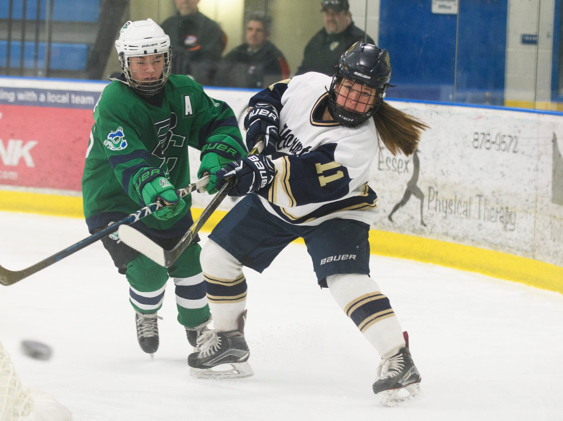 Essex's Francesca Martin (11) passes the puck as she skates past Burlington/Colchester's Olivia Maher (10) during the girls semi final hockey game between the Burlington/Colchester Sea Lakers vs. Essex Hornets at Essex skating rink on Saturday afternoon March 9, 2019 in Essex, Vermont.