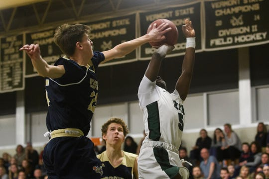 Essex's Mitchell Moffatt (25) blocks the shot by Rice's Mo Awayle (5) during the boys quarterfinal basketball game between the Essex Hornets and the Rice Green Knights at Rice Memorial High School on Friday night March 8, 2019 in South Burlington, Vermont.