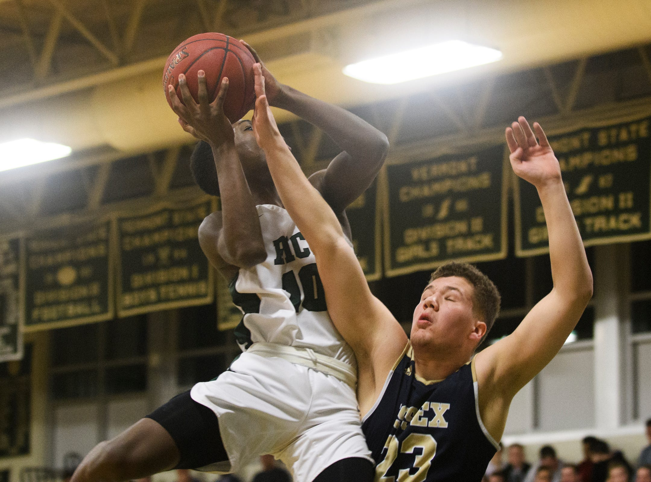 Rice's Leo Chaikin (10) leaps for a lay up over Essex's Anthony Decarvalho (23) during the boys quarterfinal basketball game between the Essex Hornets and the Rice Green Knights at Rice Memorial High School on Friday night March 8, 2019 in South Burlington, Vermont.