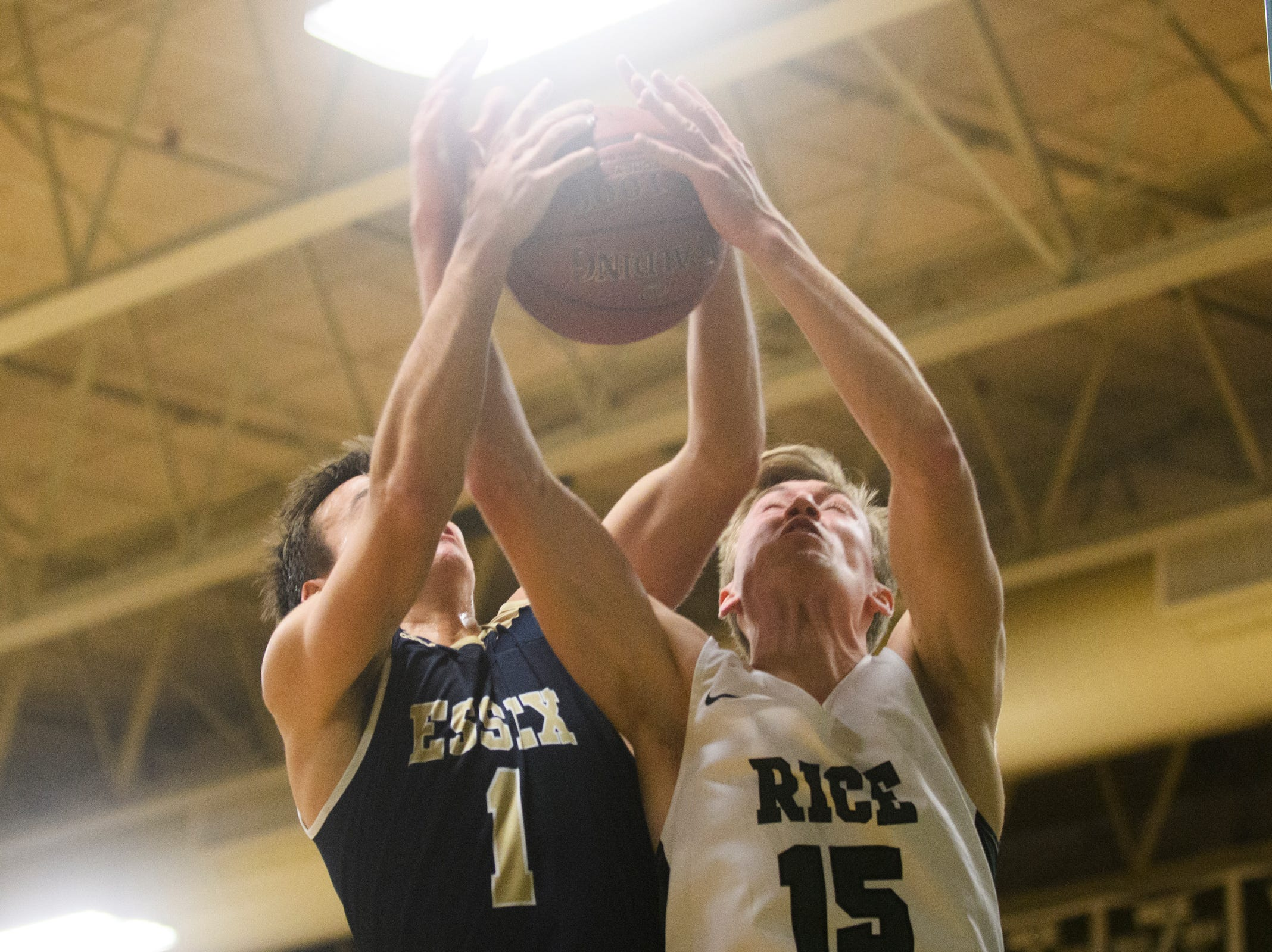 Rice's Andrew Snell (15) and Essex's Robbie Meslin (1) battle for the rebound during the boys quarterfinal basketball game between the Essex Hornets and the Rice Green Knights at Rice Memorial High School on Friday night March 8, 2019 in South Burlington, Vermont.