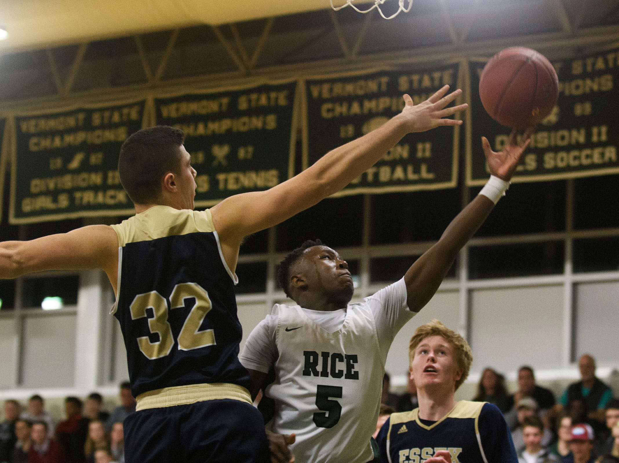 Rice's Mo Awayle (5) leaps for a lay up past Essex's Adin Peco (32) during the boys quarterfinal basketball game between the Essex Hornets and the Rice Green Knights at Rice Memorial High School on Friday night March 8, 2019 in South Burlington, Vermont.