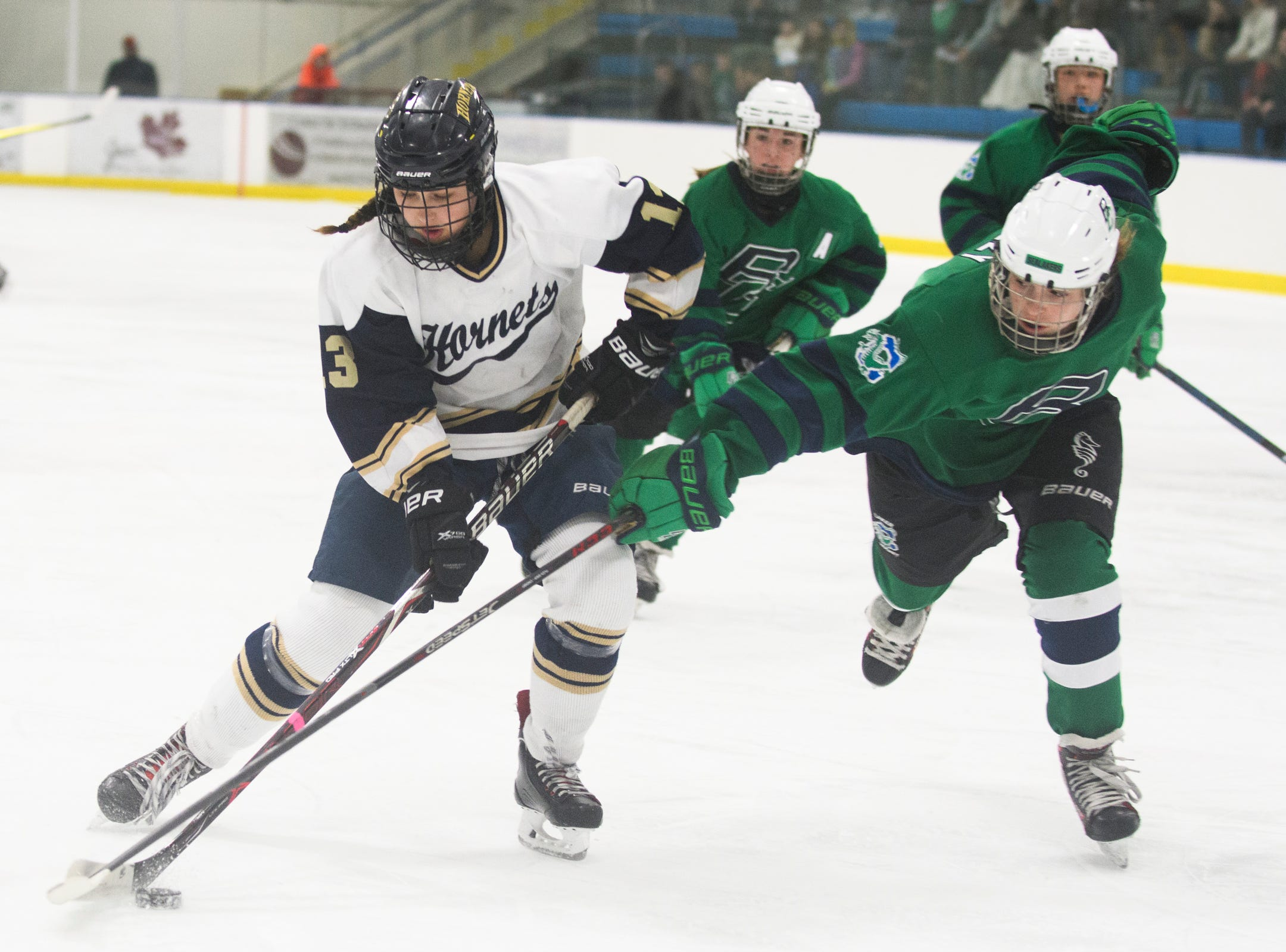 Burlington/Colchester's Kendall Muzzy (24) battles for the puck with Essex's Abigail Robbins (13) during the girls semi final hockey game between the Burlington/Colchester Sea Lakers vs. Essex Hornets at Essex skating rink on Saturday afternoon March 9, 2019 in Essex, Vermont.