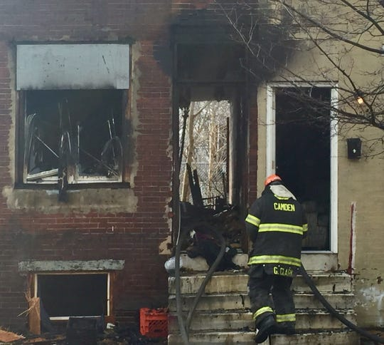 Firefighters enter a burned-out house on the 800 block of Line Street, Camden, in a March 2019 file photo.