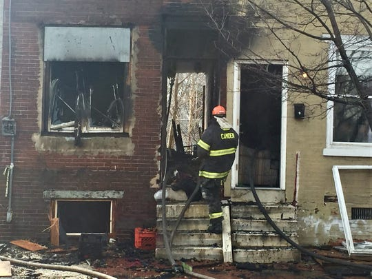 A Camden City firefighter enters a burned-out house on the 800 block of Line Street Friday.