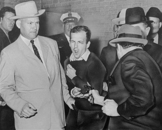 Lee Harvey Oswald, accused assassin of President John F. Kennedy, reacts as he is shot by Dallas night club owner Jack Ruby, foreground, on Nov. 24, 1963.