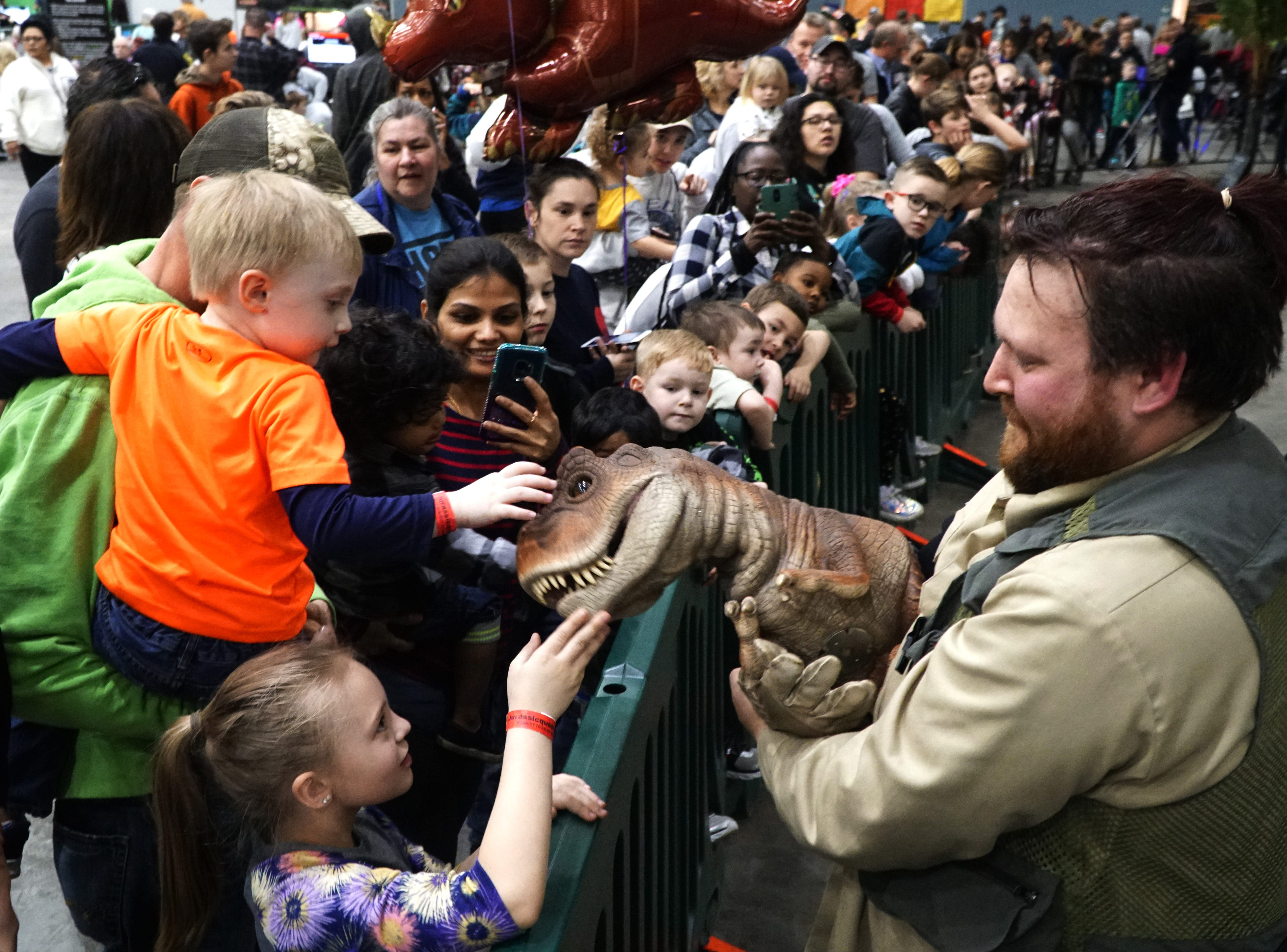 """Kids squeezed with delight as Chris Simeon maneuvered """"Tyson"""" the t-rex to nibble fingers at Jurassic Quest, March 9, 2019."""