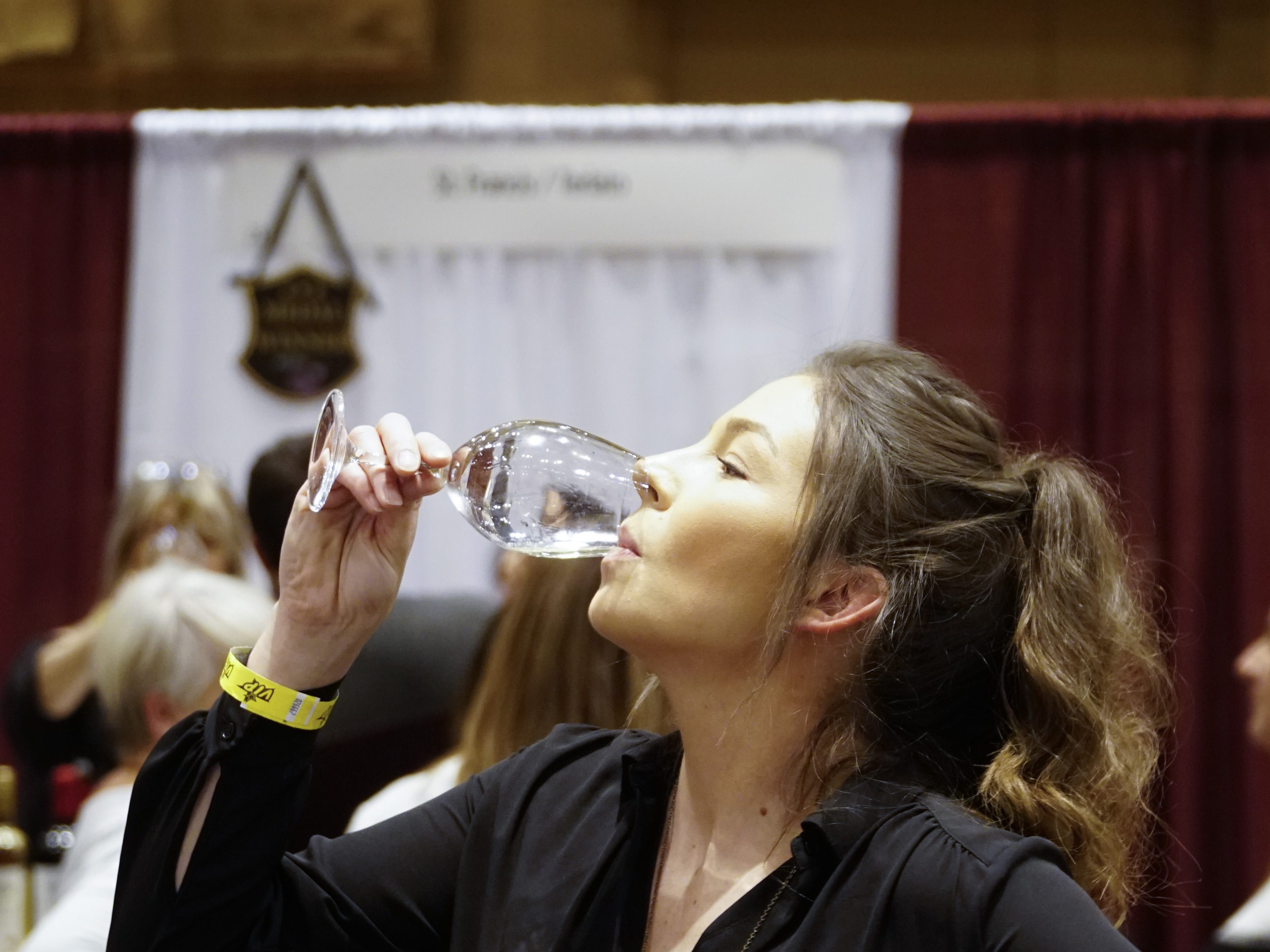 Kasey Bird finishes a glass of McManis chardonnay at The Cincinnati International Wine Festival, March 9, 2019.
