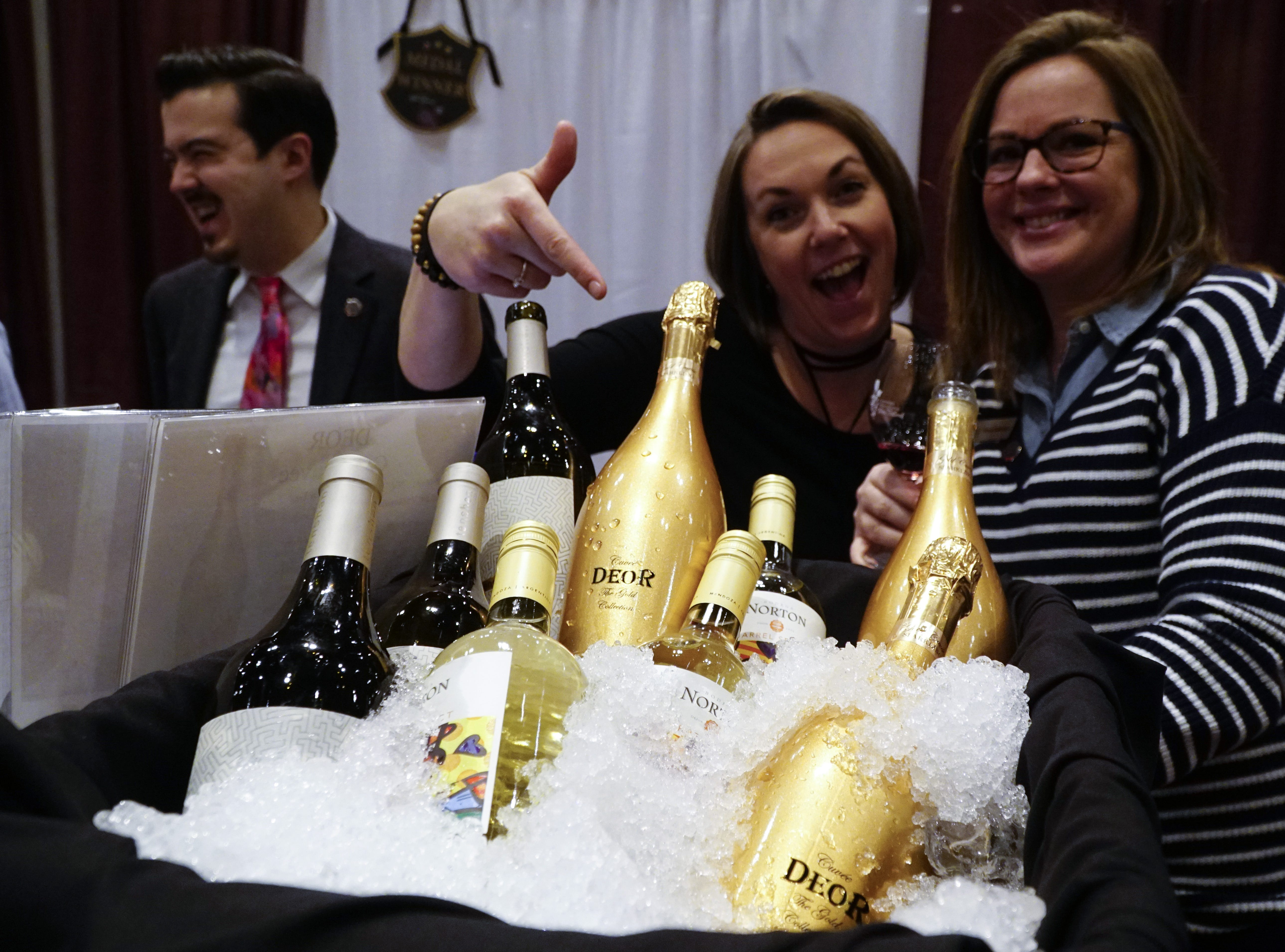 Kara York and Nikki Mulholland of Wine Trends, an Ohio artisanal wine distributor, pose next to a case of Deor, an Italian sparkling wine at The Cincinnati International Wine Festival, March 9, 2019.