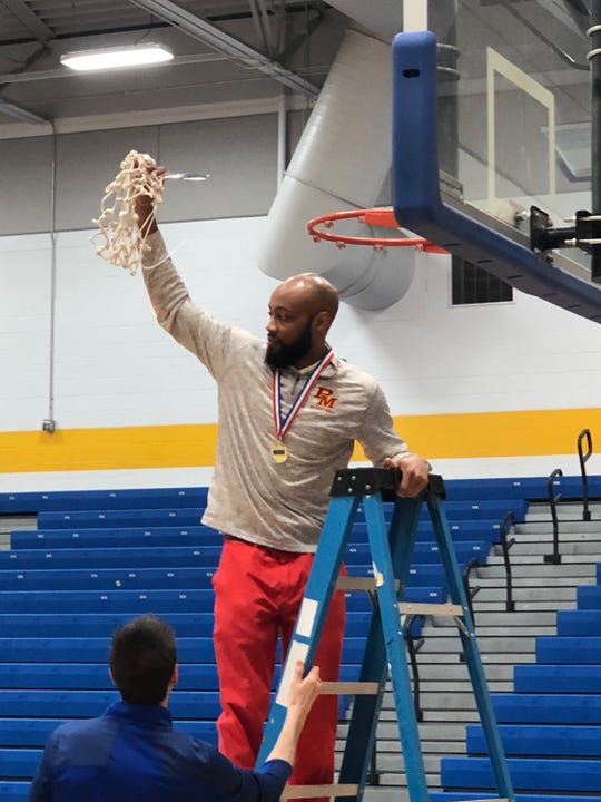 Purcell Marian head coach Jamar Mosley cuts down the championship net after the Cavaliers beat West Liberty-Salem, 51-32, for a district title Saturday March 2, 2019 at Springfield High School.
