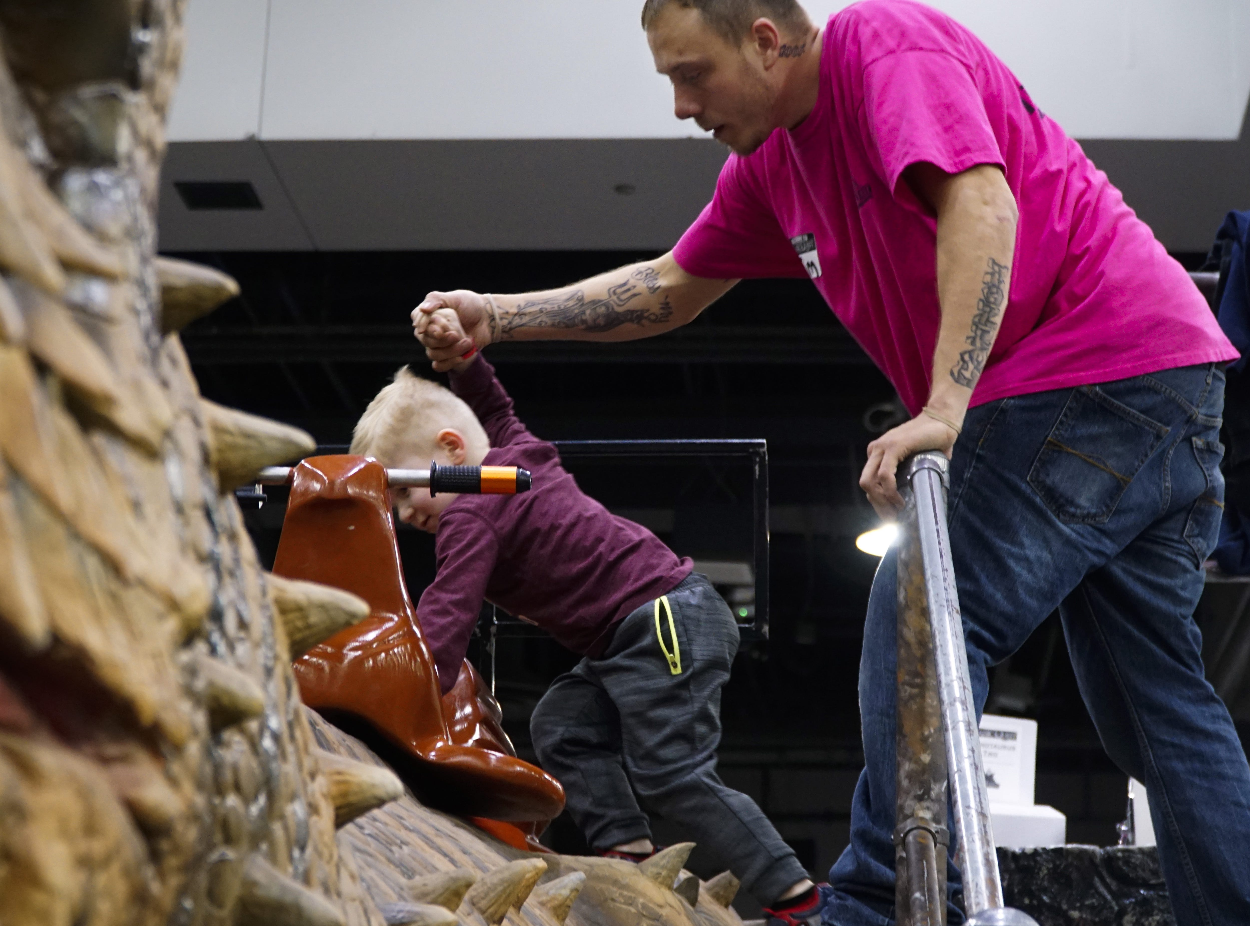 """Timothy Tackett holds the hand of a young rider at his first day working the dinosaur rides at Jurassic Quest, March 9, 2019. """"It's nice working with kids,"""" said Tackett, who spent most of the afternoon carrying younger attendees to their parents"""