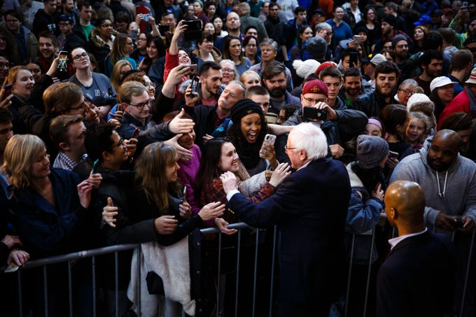 People greet democratic presidential candidate Bernie Sanders during a rally at the Iowa State Fairgrounds on Saturday, March 9, 2019 in Des Moines.