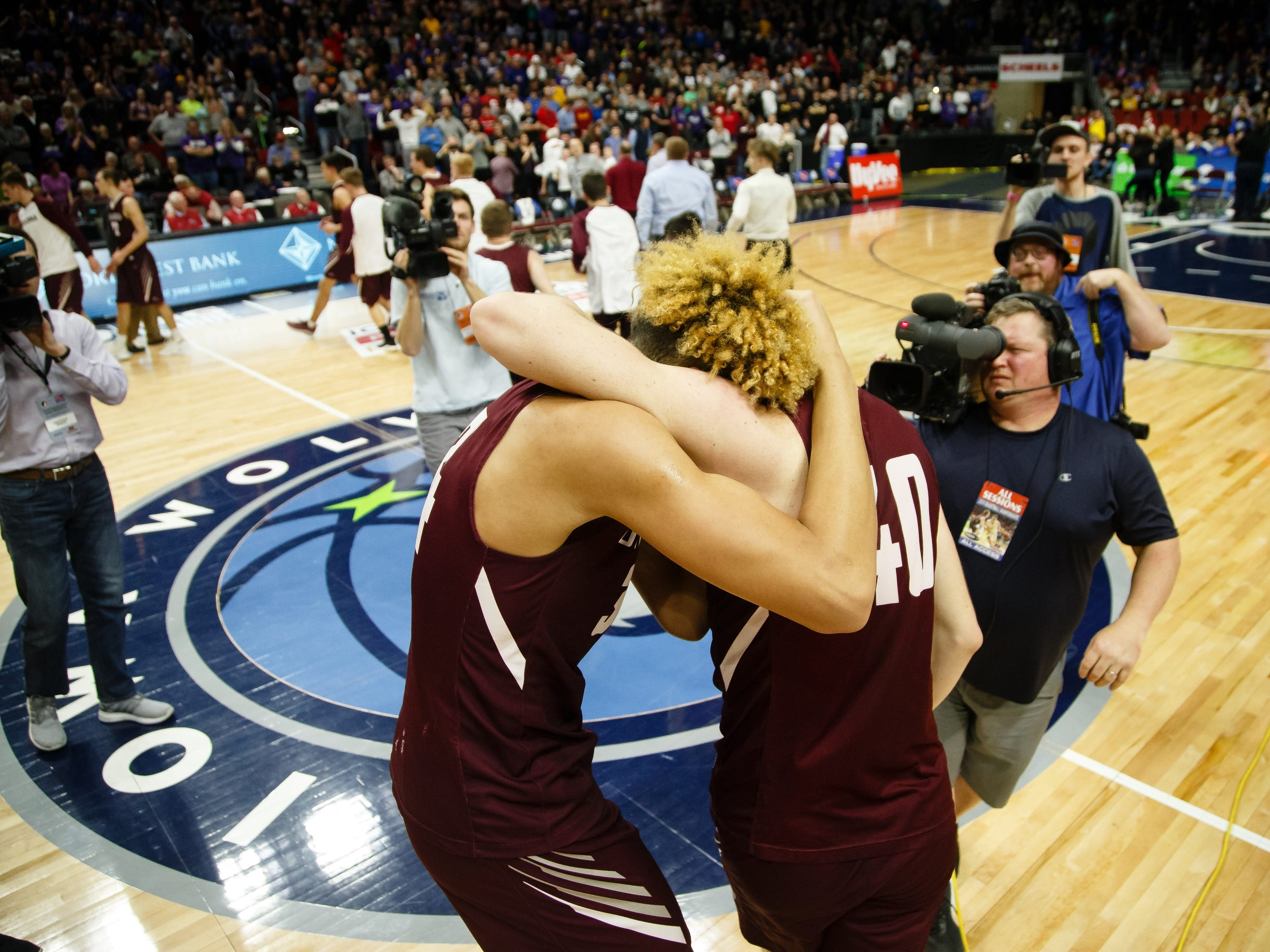 Oskaloosa's Xavier Foster (34) and Oskaloosa's Cole Henry (40) hug after Oskaloosa defeated Norwalk 48-44 to win the boys 3A state basketball championship game on Friday, March 8, 2019 in Des Moines.