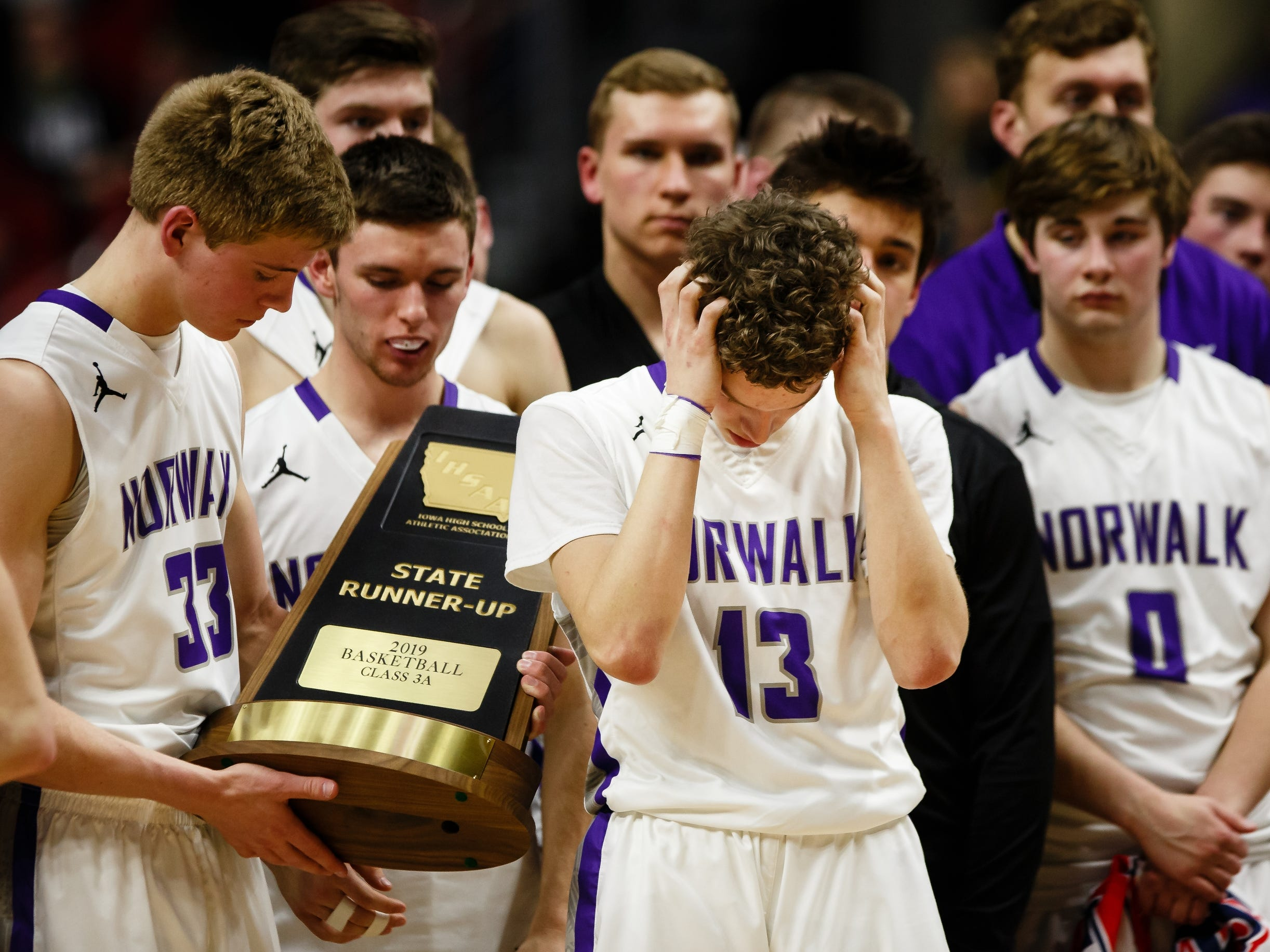 Norwalk's Bowen Born (13) reacts as teammate Norwalk's Sam Rohrer (33) holds their state runner-up trophy after loosing to Oskaloosa 48-44 during their boys 3A state basketball championship game on Friday, March 8, 2019 in Des Moines.