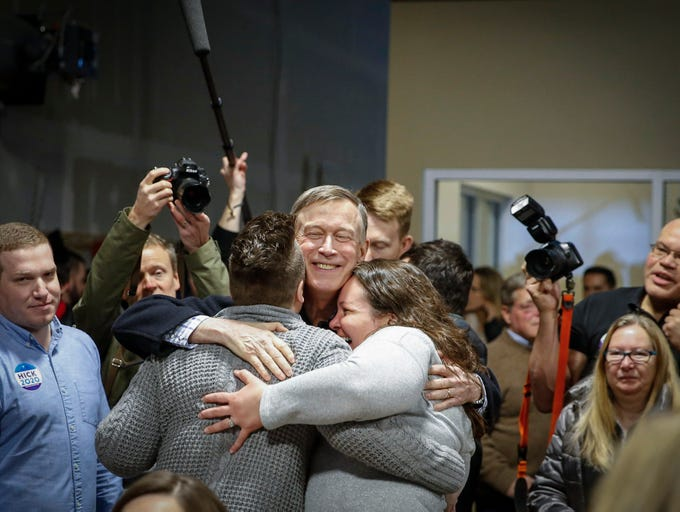 John Hickenlooper, former Colorado governor and current Democratic presidential candidate hopeful, gets a hug from supporters upon entering Confluence Brewery in Des Moines during a campaign stop on Friday, March 8, 2019.