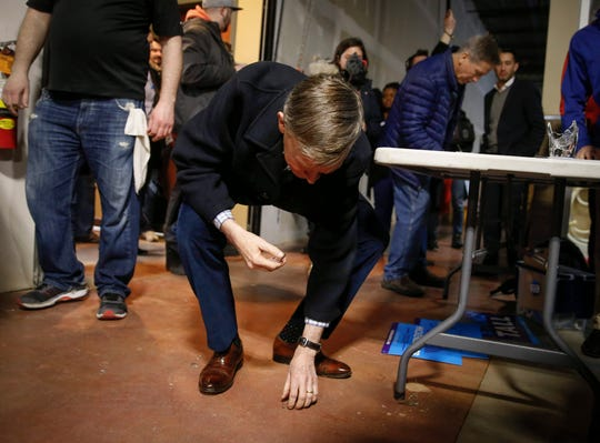 John Hickenlooper, former Colorado governor and current Democratic presidential candidate hopeful, picks up pieces of broken glass before greeting supporters during a stop at Confluence Brewery in Des Moines on Friday, March 8, 2019.