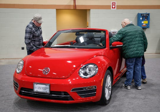 Car enthusiasts take a look at a Volkswagen Bug during the Des Moines Register All Iowa Auto Show on Saturday, March 9, 2019, at the Iowa Events Center in Des Moines. on Saturday, March 9, 2019, at the Des Moines Events Center in Des Moines.