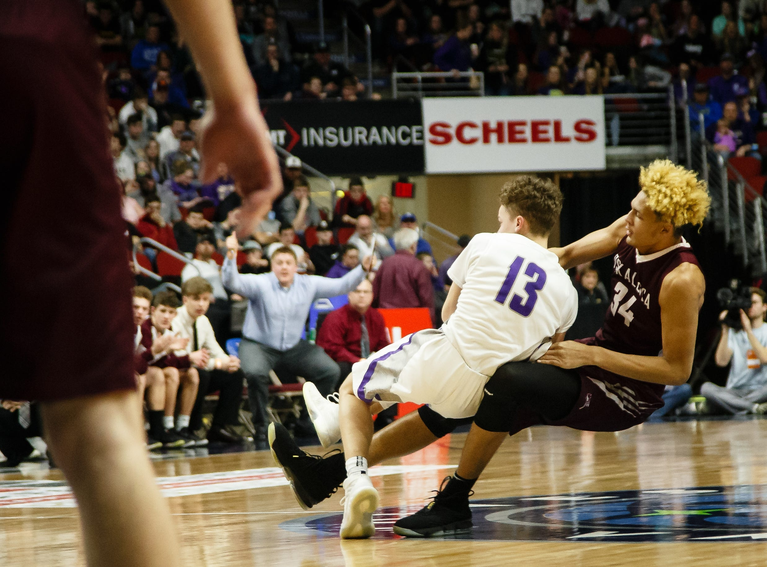 Norwalk's Bowen Born (13) and Oskaloosa's Xavier Foster (34) fight for the ball during their boys 3A state basketball championship game on Friday, March 8, 2019 in Des Moines. Oskaloosa would go on to defeat Norwalk 48-44 to win the 3A championship.