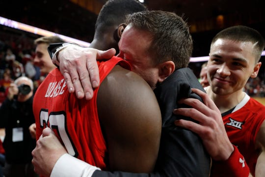 Texas Tech head coach Chris Beard, center, gets a hug from center Norense Odiase, left, after an NCAA college basketball game against Iowa State, Saturday, March 9, 2019, in Ames, Iowa. Texas Tech won 80-73.