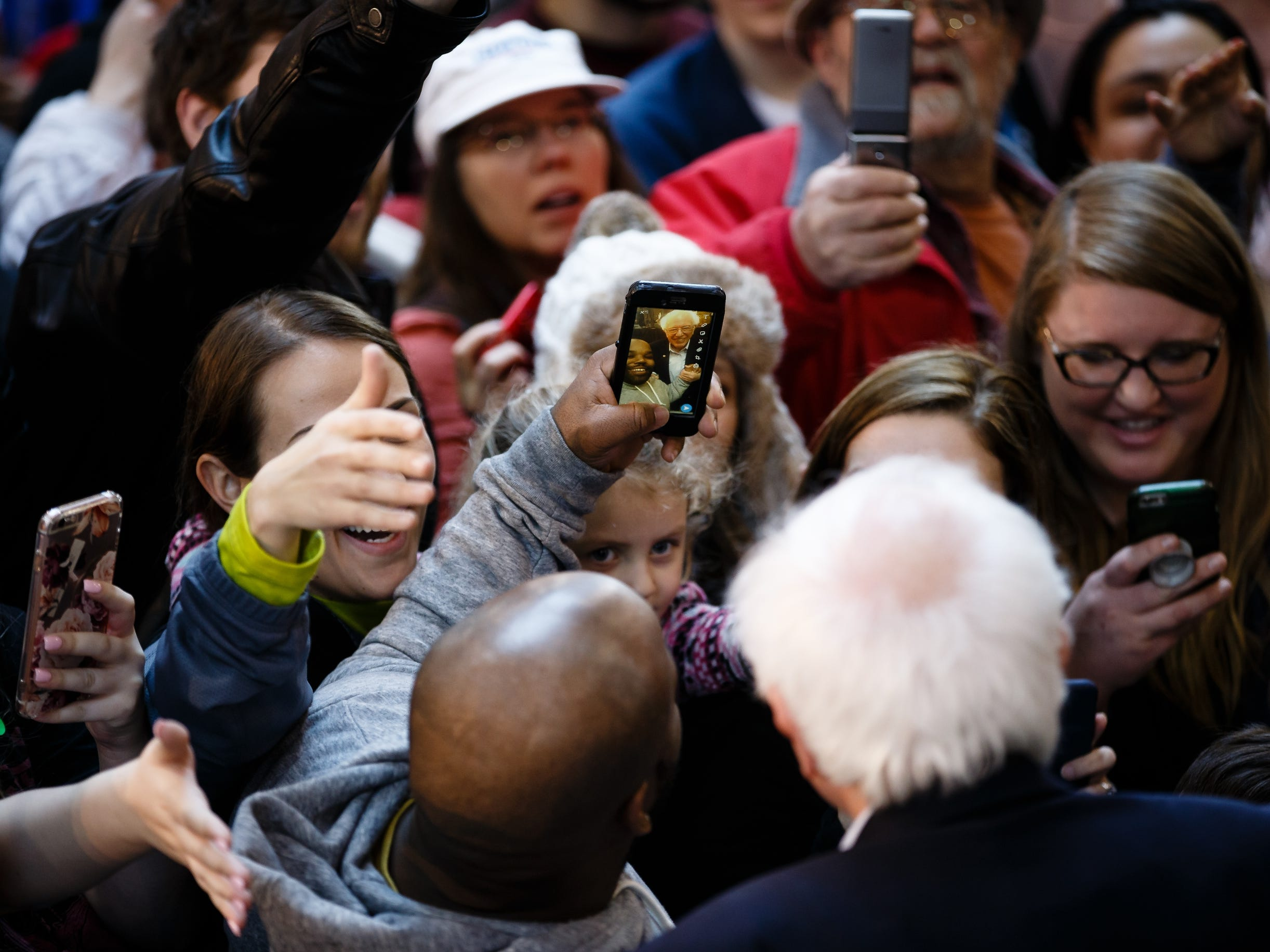 People take a selfie with democratic presidential candidate Bernie Sanders during a rally at the Iowa State Fairgrounds on Saturday, March 9, 2019 in Des Moines.