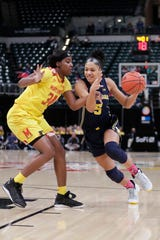Michigan forward Kayla Robbins drives on Maryland forward Brianna Fraser in the first half of the Big Ten women's tournament in Indianapolis on Saturday, March 9, 2019.