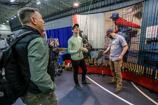 Connor Ford, 17, of Holly looks to purchase a Redington fly rod from Redington Community Manager Jay Beebe, 33, of Seattle, during the Midwest Fly Fishing Expo at Macomb Community College Sports and Expo Center in Warren, Mich. on Saturday, March 9, 2019.