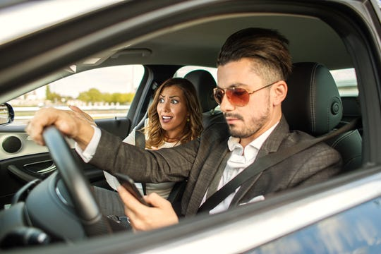 Couple driving in car while man is texting and woman is worried